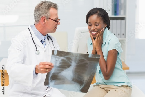 Doctor showing young patient her positive chest xray