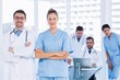 Doctors with colleagues using laptop in medical office