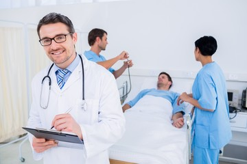 Doctor writing reports with patient and surgeons in background