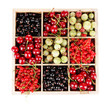 Different summer berries in wooden crate isolated on white