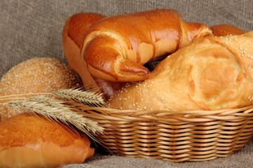 Baked bread in wicker basket on burlap background