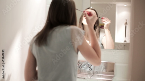 Young woman applying mascara makeup in front of the mirror