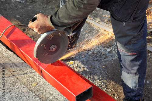 Cutting tube, workers hands, angle grinder tool and sparks