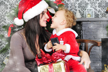 a little boy near the tree with her mother in a Santa suit