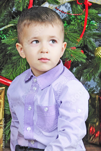 small boy near new year's fir tree