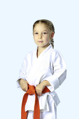 Little serious girl in a kimono with orange belt