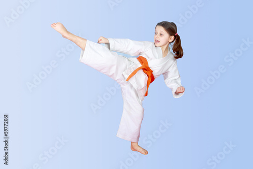 On a light background little athlete beat high leg kick