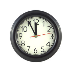Big round wall clock shows almost twelve isolated close up