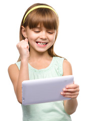Young girl is playing game using tablet