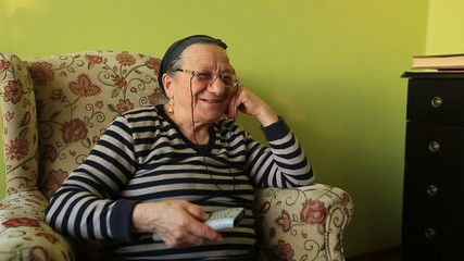 elderly woman watching television at home