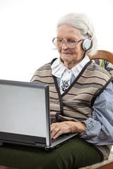 Senior woman using laptop computer isolated on white