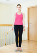 cheerful girl standing on bathroom scales