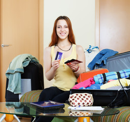Smiling woman and packing suitcase