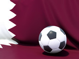 Flag of qatar with football in front of it
