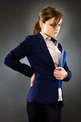 Portrait of a young businesswoman with back pain