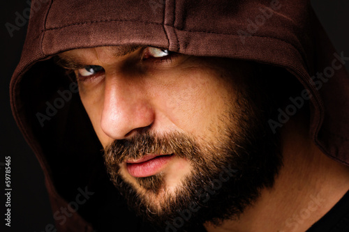 Close-up portrait of threatening  man with beard wearing a hood