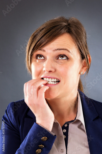 Closeup portrait of a nervous young businesswoman biting her fin