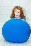 Happy girl doing gymnastics on blue ball.