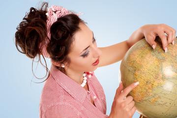hübsche Frau zeigt auf Globus