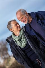 glückliche lachende senioren paar arm in arm im freien