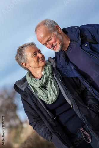 Leinwanddruck Bild glückliche lachende senioren paar arm in arm im freien