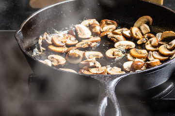 Sauteing sliced mushrooms in a skillet