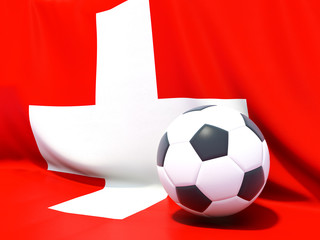 Flag of switzerland with football in front of it