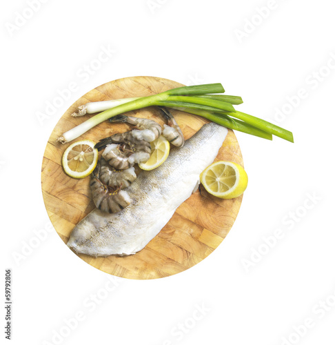Raw fish fillets , shrimp , lemon and onions on white background