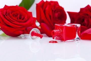 eleganter roter nagellack in glasflasche mit roten rosen