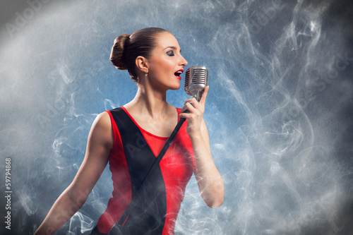 beautiful blonde woman singer with a microphone