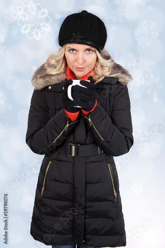 Blonde Frau wärmt sich an einer Tasse