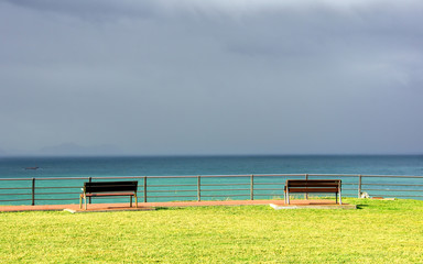 benches on cliff with sea and stormy clouds