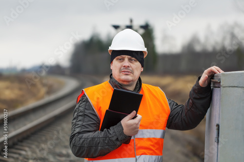 Railroad employee with tablet PC near railway