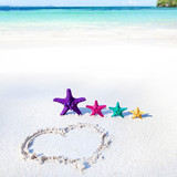 Heart on beach with color starfishes
