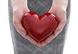 Frau hält ein Herz in Rot in der Hand
