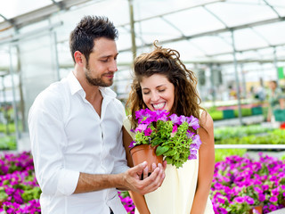 couple have fun choosing flower pots in a greenhouse