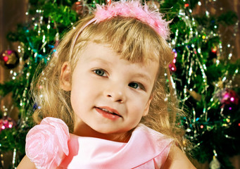 Portrait of young girl in pink on background Christmas trees