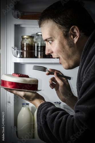 Young happy man eating cake from the fridge