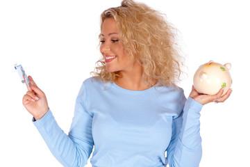 Blonde junge Frau mit Geldschein und Sparschwein in der Hand