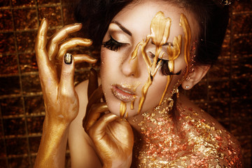 Closeup portrait of beautiful brunette in liquid gold