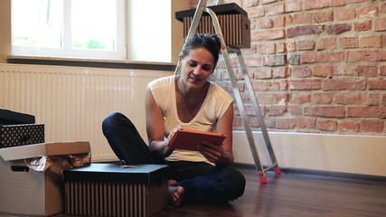 happy woman planning to furnish her flat with a tablet