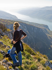Girl taking a rest at 2000 feet vertical cliff over Danube river
