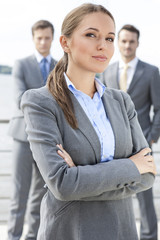 Portrait of confident businesswoman standing arms crossed with coworkers in background on terrace