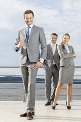 Full length portrait of confident businessman gesturing thumbs up while standing with coworkers on terrace against sky