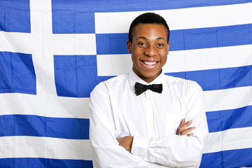 Portrait of happy man with arms crossed against Greek flag