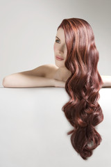 Thoughtful woman with long red dyed hair against gray background