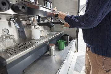 Midsection of man cleaning coffee machine at mobile shop