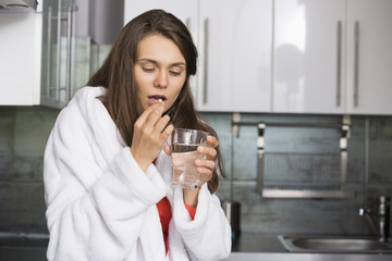 Ill woman taking medicine in kitchen