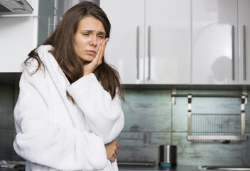 Sad woman suffering from toothache standing in kitchen