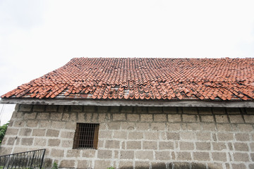 House with tiled roof and stone wall in Manila; Philippines